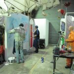 Two men painting a canvas backdrop with a mannequin spectator. All taking place at the Mayo Artsquad website.